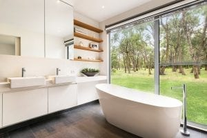 Modern bathroom interior with white oval bathtub and window view of green trees.