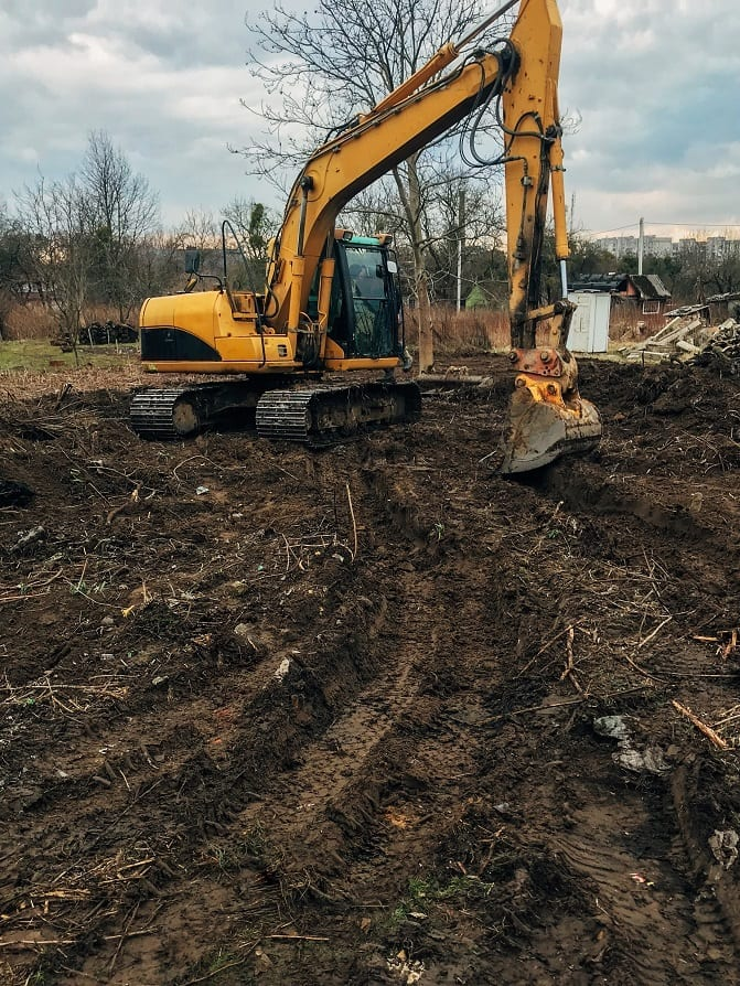 Bulldozer clearing land from old trees, roots and branches